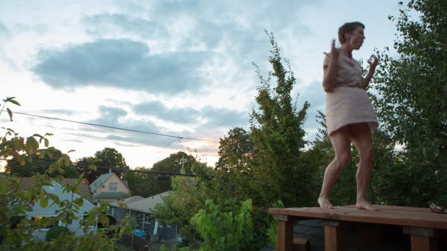 handheld shot of woman dancing on wooden floor against sky during sunset - portland oregon homes stock videos & royalty-free footage