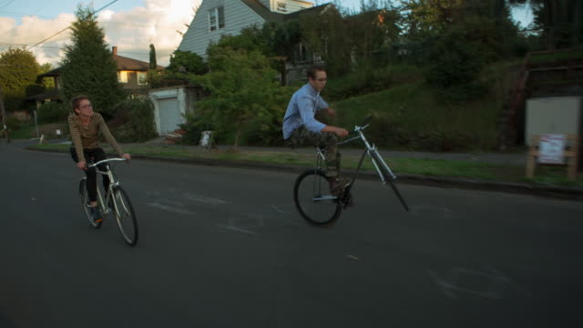 handheld shot of woman looking at male friend performing stunt while cycling on road against houses - portland oregon bike stock videos & royalty-free footage