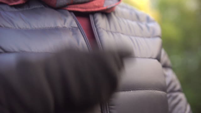 vidéos et rushes de handheld shot of woman zipping black padded jacket outdoors - veste et blouson
