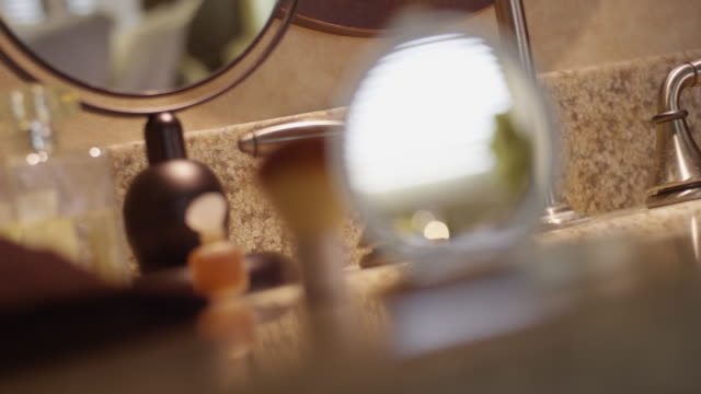 vídeos de stock, filmes e b-roll de handheld shot of woman's compact with mirror sitting on a bathroom counter, rack focus to the waiting tea set and stuffed frog in the background. - pincel de maquiagem