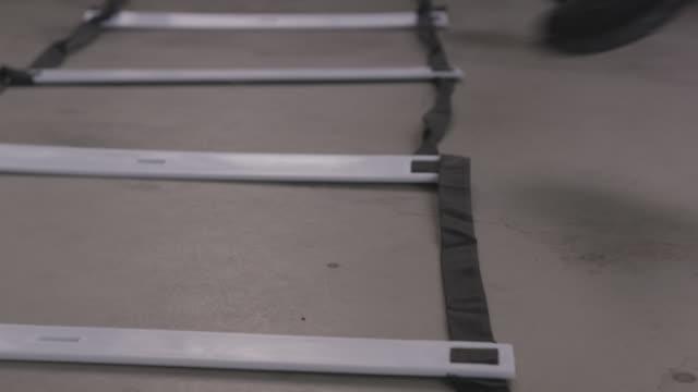 vidéos et rushes de handheld shot of women using agility ladder while exercising in gym - quête de beauté