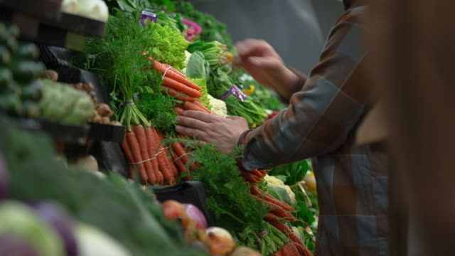 handheld shot of worker arranging vegetables on retail display at store - carrot stock videos & royalty-free footage