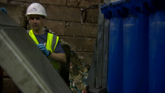 Handheld shot of worker removing a blue wheelie bin from back of delivery truck