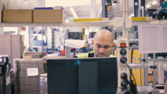 handheld shot of worker using desktop computer in warehouse - dokument stock-videos und b-roll-filmmaterial
