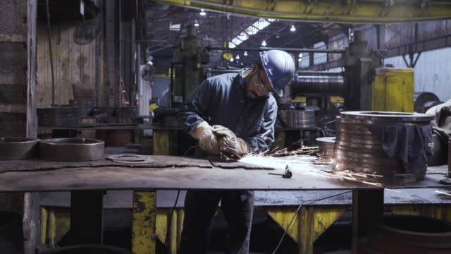 vidéos et rushes de handheld shot of worker welding at table in workshop - aciérie