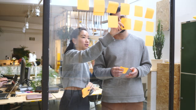 handheld shot of young business colleagues discussing over adhesive notes on glass wall in new office - brainstorming stock videos & royalty-free footage