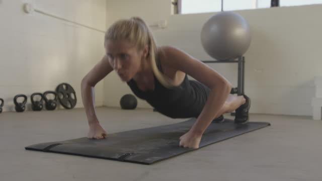 vídeos y material grabado en eventos de stock de handheld shot of young female athlete doing push-ups on exercise mat at gym - entrenamiento sin material