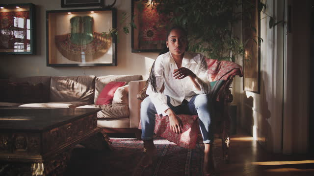 stockvideo's en b-roll-footage met handheld shot of young female influencer entering living room and sitting on armchair at home - shaky