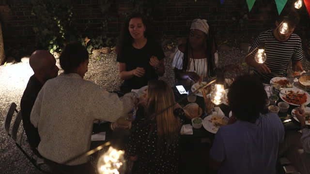 handheld shot of young multi-ethnic friends enjoying dinner during garden party at night - community stock videos & royalty-free footage