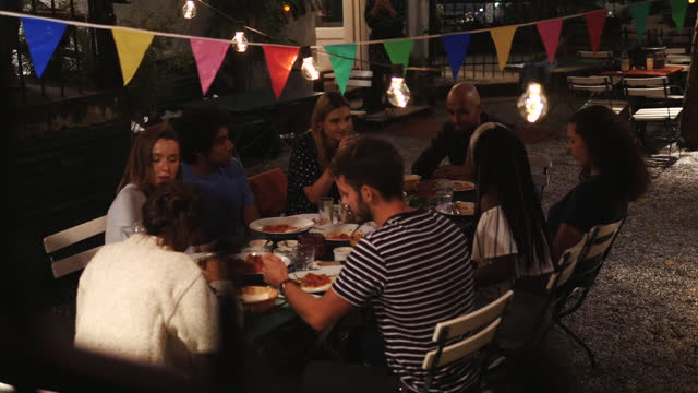 handheld shot of young multi-ethnic friends talking while enjoying dinner party in back yard at night - 20 29 years stock videos & royalty-free footage