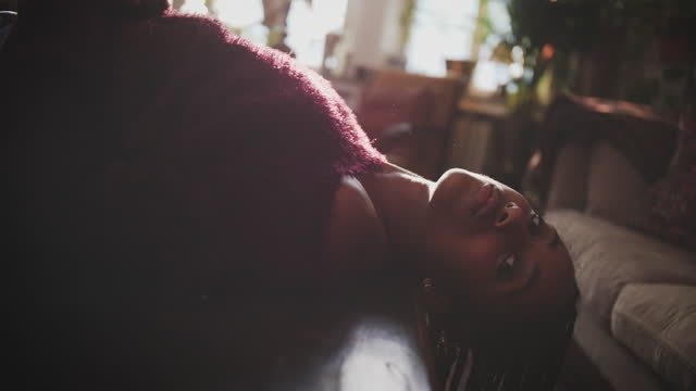 Handheld shot of young woman in magenta sweater lying on coffee table in living room at home