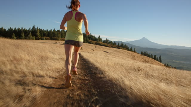 handheld shot of young woman running on trail against mountains during sunny day - joggerin stock-videos und b-roll-filmmaterial