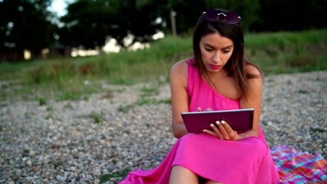 vídeos de stock e filmes b-roll de handheld shot oh beautiful young woman using tablet on the beach by the lake - trabalhadora de colarinho branco