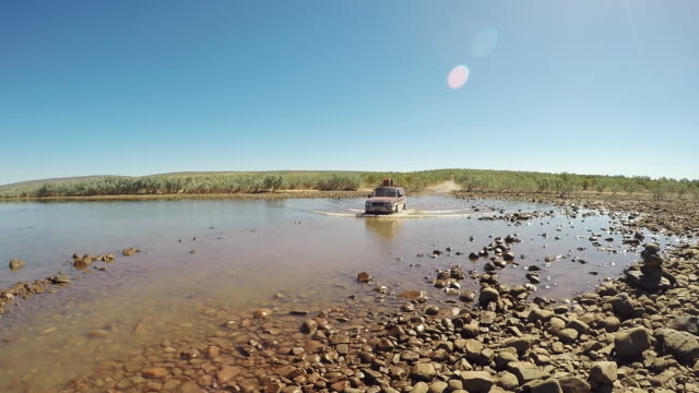 handheld shot showing a 4x4 driving through the pentecost river crossing during dry season, gibb river road, the kimberley, western australia, australia - ペンテコステ点の映像素材/bロール