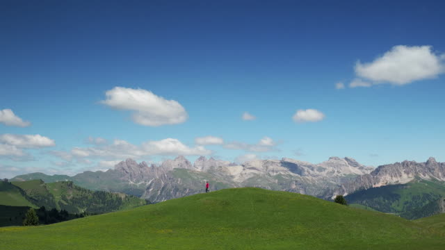 handheld shot showing a person walking on a hill with a mountainous backdrop, val gardena, dolomites, italy - val gardena stock videos & royalty-free footage