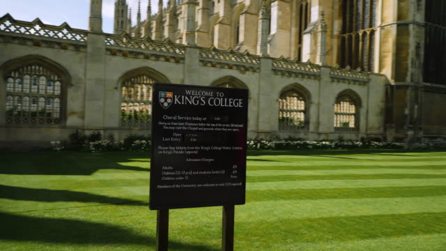 handheld shot sweeping around a sign displaying admission prices to the chapel at king's college, university of cambridge, uk. - cambridge university stock videos and b-roll footage