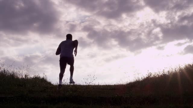 vídeos de stock e filmes b-roll de ws handheld silhouette  male athlete running up hill  - hill