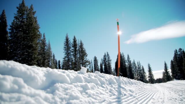 handheld slow motion low angle shot of trail depth marker with sun flare in deep snow outdoors - depth marker stock videos & royalty-free footage