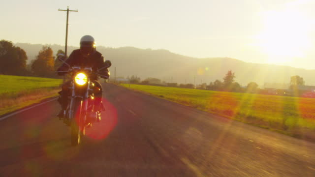 Handheld slow motion of biker riding motorcycle on road against sky during sunset