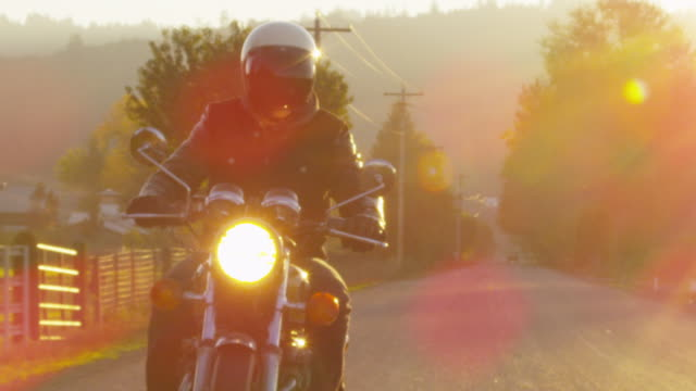 Handheld slow motion of biker riding motorcycle on road during sunset