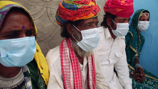 handheld slow-motion of four village people, two males and two females, seated together and looking off camera and having a discussion while they all wear surgical masks for prevention from a global pandemic - rural scene stock videos & royalty-free footage