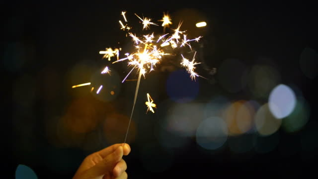 夜の時間に輝くハンドヘルドスパークラー花火 - 正月点の映像素材/bロール