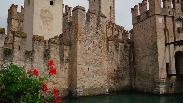 handheld tilt down shot showing scaligero castle, lake garda, sirmione, italy - moat stock videos & royalty-free footage