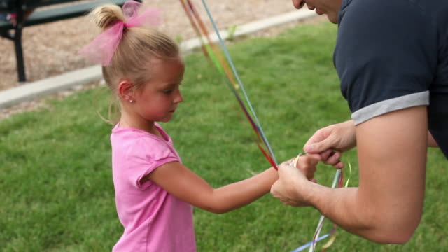 handheld tilt of a little girl and balloon strings. - hair bow stock videos & royalty-free footage