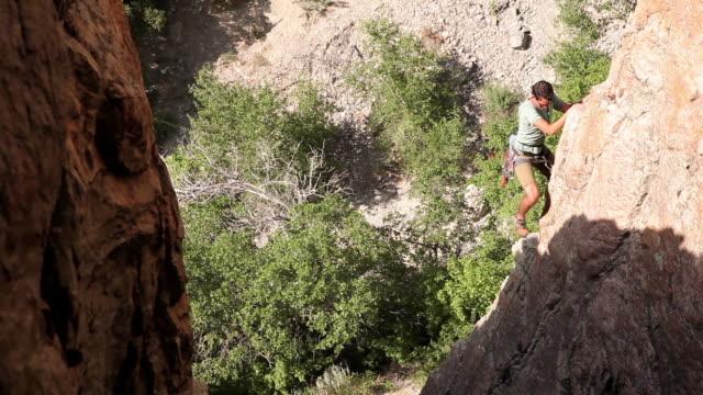 Handheld tilt of a man climbing a rock wall in the sunshine.