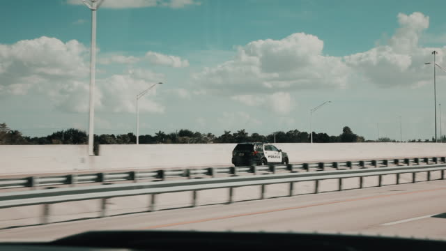 handheld tracking shot showing a police vehicle on a highway, miami, florida, united states of america - politics abstract stock videos & royalty-free footage
