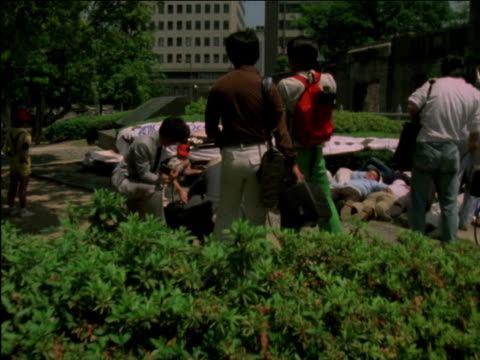 hand-held travelling shot up to a group of peace protesters lying on ground - playing dead - at foot of a-bomb dome inside peace memorial park in... - 大量破壊兵器点の映像素材/bロール