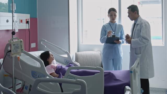 vídeos de stock, filmes e b-roll de vídeo portátil da equipe de médico asiático discutindo no quarto do hospital - recuperação