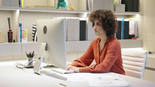 Vídeo portátil de arquiteta feminina trabalhando em mesa no escritório moderno