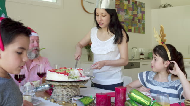 Handheld video of mother cutting a portion of Pavlova cake at Christmas lunch
