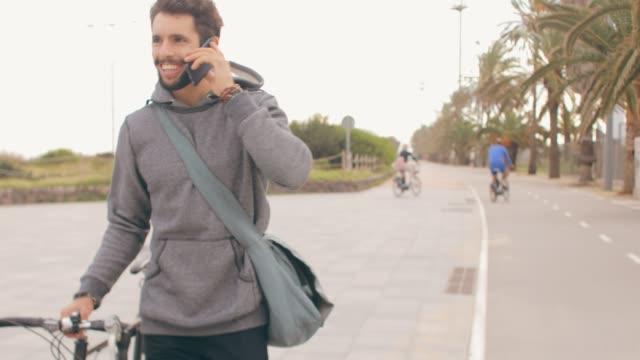 vídeos de stock, filmes e b-roll de tiro de vídeo portátil de jovem com uma bicicleta. - bolsa tiracolo bolsa