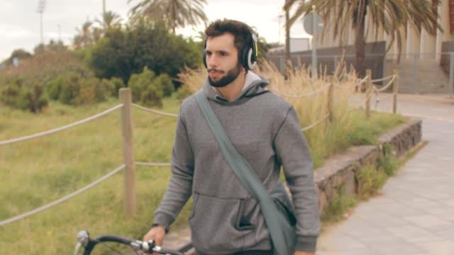 vidéos et rushes de ordinateur de poche vidéo coup de jeune homme avec un vélo. - sac
