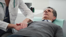 Handheld video shows of doctor examining stomach of senior man. Shot with RED helium camera in 8K