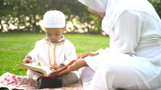 handheld view : muslim mother teach her son to read  quran in public park - eid mubarak stock videos & royalty-free footage