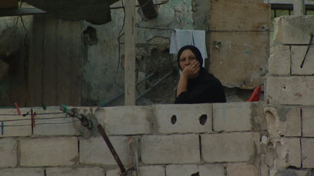 vídeos de stock, filmes e b-roll de hand-held view of a palestinian woman sitting with her face in her hand staring out of her backyard in the mieh mieh palestinian refugee camp, at... - staring