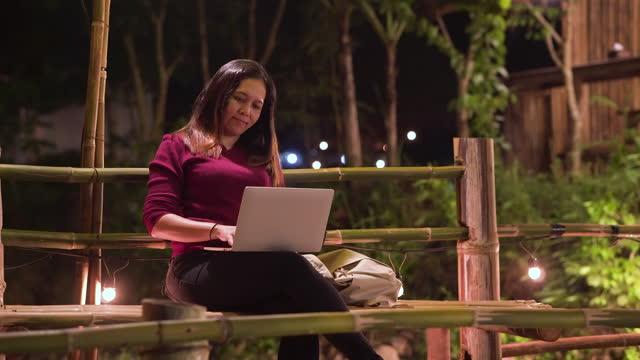 handheld-ansicht der asiatischen frau in winterkleidung reisen auf einem lokalen natürlichen ziel, sitzen auf der bambusbrücke für eine pause in urlaub in südostasien, immer arbeiten an einem laptop für globale geschäfts-und geschäftstreffen. - bamboo plant stock-videos und b-roll-filmmaterial