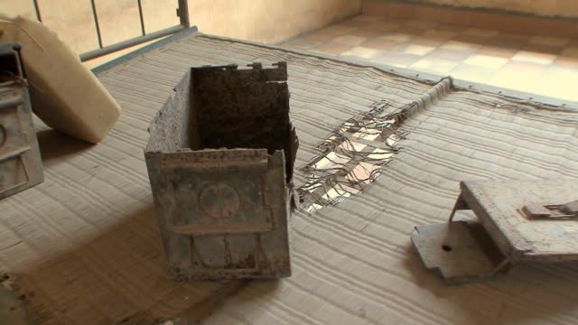cu hand-held view of bed with canisters holding food and water in cell at tuol sleng school, phnom penh, cambodia - genocide stock videos & royalty-free footage