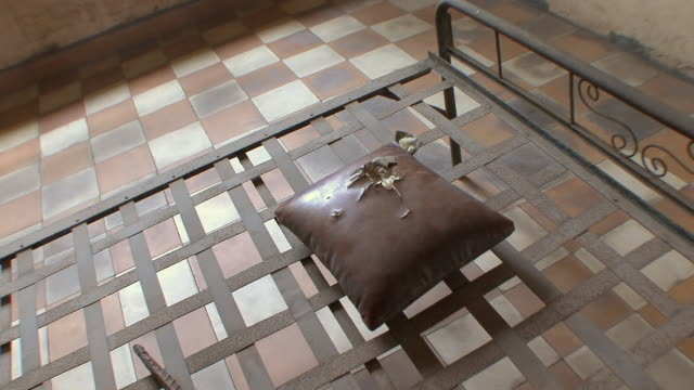 cu hand-held view of bed with instrument of torture and torn pillow in cell at tuol sleng school, phnom penh, cambodia - instrument of torture stock videos & royalty-free footage