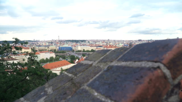 handheld view of orange roof of old Prague city behind old wall in evening