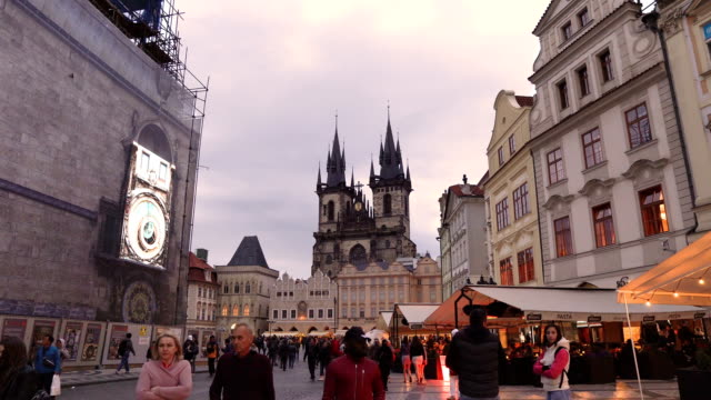 handheld view: old square containing crowd of traveller in Prague at evening, Czech Republic