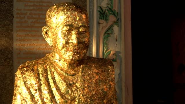 vídeos de stock e filmes b-roll de handheld view: representative famous monk statue with gold leaf - modelo objeto