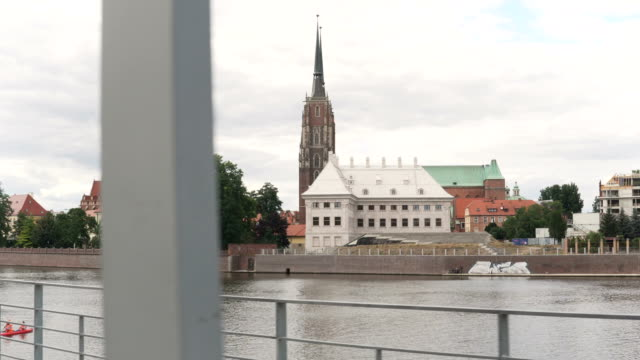 handheld view: walking along river bank to see Cathedral Island in Wroclaw, Poland
