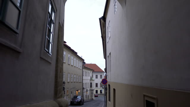 handheld view: walking out from small gate between tall building in local street in prague - traditionally czech stock videos & royalty-free footage