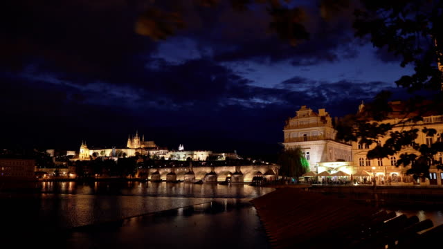 handheld view while walking to see charles bridge at prague at night from vltava river, czech republic - charles bridge stock videos & royalty-free footage