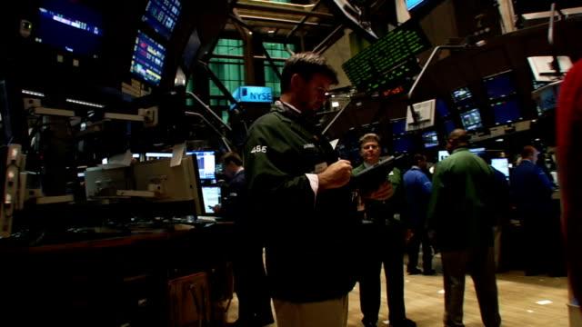 vídeos de stock e filmes b-roll de handheld waistlevel view of monitors and fastpaced traders walking through trading floor of new york stock exchange new york city - negociante ocupação financeira