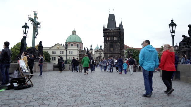 handheld walking view: crowds of traveller on charles bridge in prague during raining day, czech republic. - prague stock videos & royalty-free footage